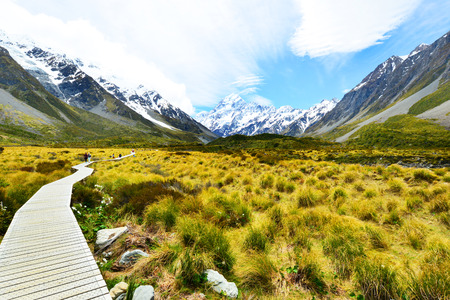 hooker: Boarded trail section in Hooker Valley on a track leading to Aoraki, Mount Cook, highest peak of Southern Alps, an icon of New Zealand partially covered in clouds