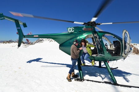 franz: FRANZ JOSEF GLACIER, NEW ZEALAND: November 16, 2014: passengers alight from a helicopter onto the snow above Franz Josef Glacier, Westland, New Zealand