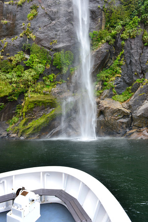 fiord: Boat near spectacular waterfall, Milford Sound fiord, New Zealand Stock Photo