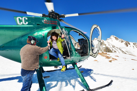 josef: FRANZ JOSEF GLACIER, NEW ZEALAND: November 16, 2014: passengers alight from a helicopter onto the snow above Franz Josef Glacier, Westland, New Zealand