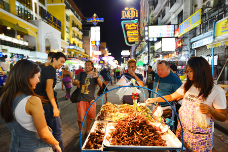 BANGKOK - April 19 :A street vendor sells fried cockroaches and other insects to tourists on Khao San Road on April 19 , 2015 in Bangkok,Thailand. There is 16,000 registered street vendors in Bangkok.