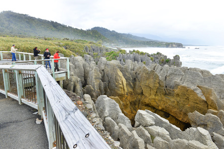 orificio nasal: PUNAKAIKI, NUEVA ZELANDA 14 de noviembre de 2014: Los turistas fotografiar a s� mismos, mientras que el espir�culo principal es en la acci�n en las rocas de la crepe, Punakaiki, Costa Oeste, Isla Sur, Nueva Zelanda