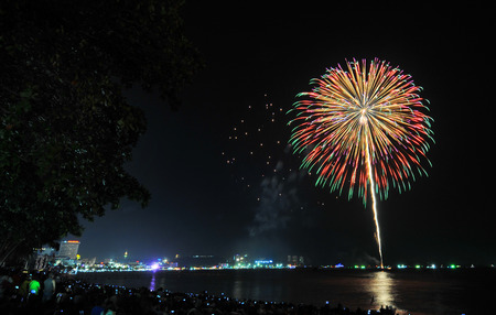 converge: Multicolor fireworks night scene, closeup with pattaya cityscape sea beach view, thailand