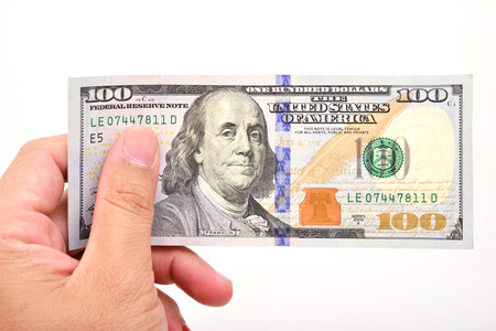 one hundred dollar bill: A mans hand holding a one hundred dollar bill.