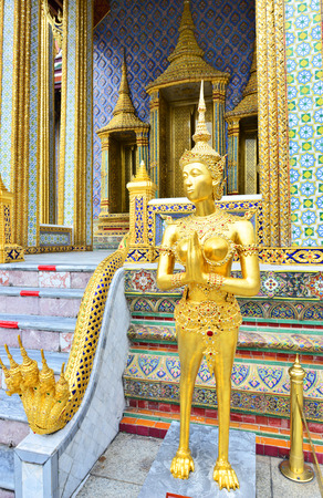 temple tank: Golden Kinnari statue at the Temple of the Emerald Buddha Wat Phra Kaew Stock Photo