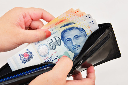 wallet with singapore dollars in the hands on a white background Stock Photo
