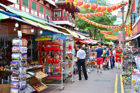 settling: SINGAPORE - NOV 17: Shoppers walk through a Chinatown market on November 17, 2015 in Singapore. The city states ethnic Chinese began settling in Chinatown circa 1820s.