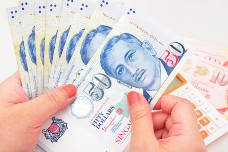 Singapore dollars in the hands on a white background Stock Photo