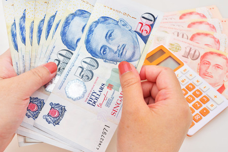 50 dollar bill: Singapore dollars in the hands on a white background Stock Photo