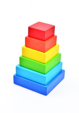 fondo para bebe: Pirámide construir a partir de piezas rectangulares de madera de colores. Juguete para los bebés y niños pequeños para aprender con alegría habilidades mecánicas y colores. Foto de estudio sobre fondo blanco.