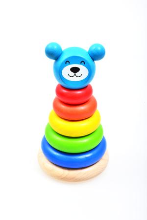 fondo para bebe: Pirámide construir a partir de madera de los anillos de colores. Juguete para los bebés y niños pequeños para aprender con alegría habilidades mecánicas y colores. Foto de estudio sobre fondo blanco. Foto de archivo