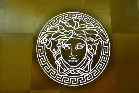 branded: SINGAPORE - NOVEMBER 18, 2015: close us shot of Versace logo on the wall. Versace, is an Italian fashion company and trade name founded by Gianni Versace in 1978 Editorial