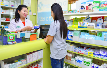 prescription: Friendly asian pharmacist in white lab coat giving young asian woman prescription drugs while standing in medicine counter