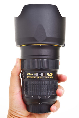 Bangkok Thailand - March 29, 2016: Man holding lens AFS-S 24-74mm 1:2.8G ED made by Nikon in Japan on white background .This lens was announced in 2007 by Nikon