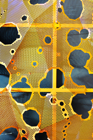 punched: Sheet of metal with holes punched on orange background
