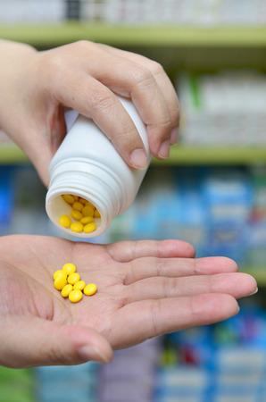 colored bottle: Pharmacist dispensing Pills into Hand in drugstore.