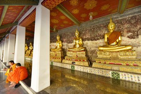 sit around: Bangkok, Thailand- MARCH 12 : Monk in traditional orange sit in front of Buddha around Wat Suthat Thep Wararam Buddhist temple on March 12,2016 in Bangkok, Thailand.