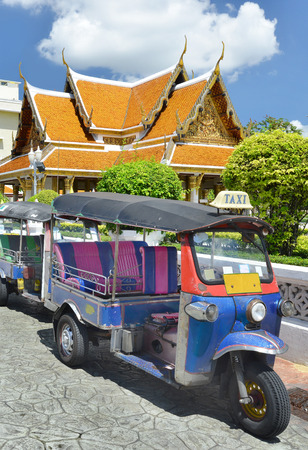 BANGKOK, THAILAND - JULY 27 : Tricycle taxi of Thailand on street and background of Wat Phra Kaew ( the Temple of the Emerald Buddha) on July 27 , 2016. Here is destinations of landmarks traveler Editorial