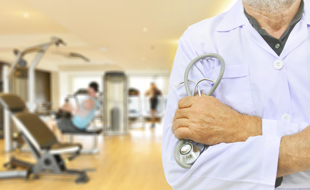 Doctor with stethoscope on fitness room background. Stock Photo