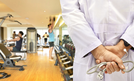 Doctor with stethoscope on fitness room background. Фото со стока