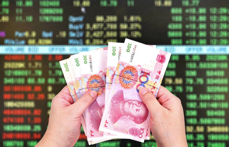 show bill: Mans hand holding a one hundred yuan bill on stock market background.