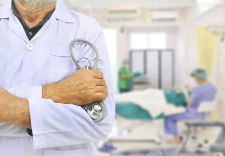 operation gown: Doctor in a white gown holds the stethoscope on blur operating room background. Stock Photo