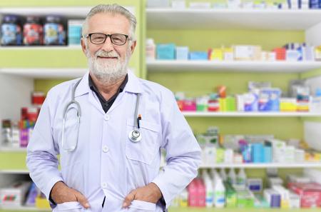 Smile senior doctor on medicine shelf background.