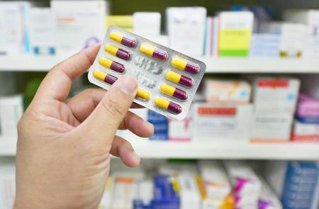 Hand holding capsule pack on blur shelf pharmacy drugstore Stock Photo