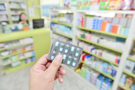 over the counter: Hand holding capsule pack on blur shelf pharmacy drugstore Stock Photo
