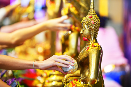 Songkran festival in Thailand,Hand use Sprinkle water onto a Buddha image.