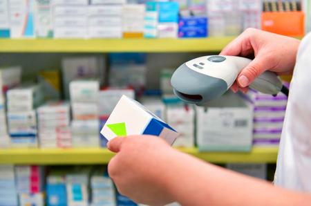 Farmacéutico escanear el código de barras de la medicina en una farmacia droguería Foto de archivo