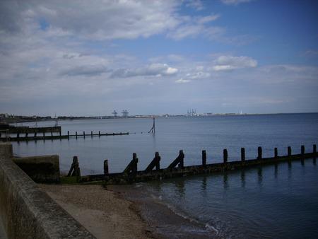breakwater: Playa de arena con el mar en calma y el rompeolas