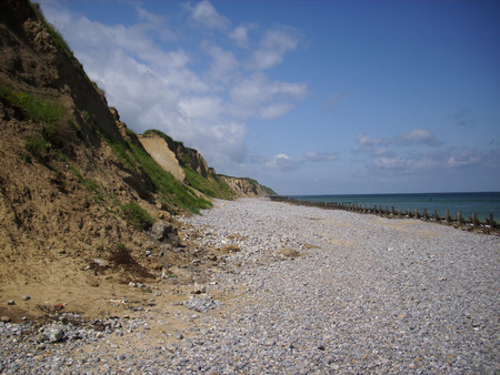 breakwaters: Shingle and sand beach with calm sea, breakwaters and cliffs