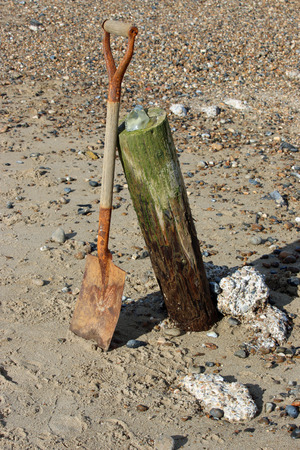 handled: Old wooden handled spade on a beach Stock Photo