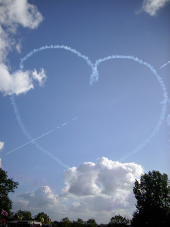 royal air force: Royal Air Force Red Arrows aerobatic display team in flight with a heart and arrow in white smoke Stock Photo