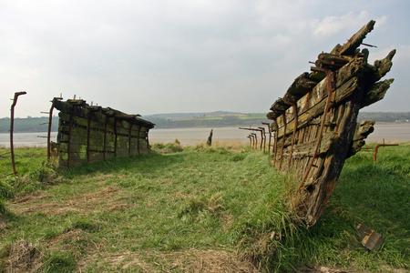 Derelict abandoned wooden barge rotting alongside a river