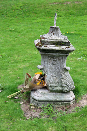 Damaged park stone ornamental jardiniere base with wilting flower bouquet. The neglect and the wilting flowers just seem to go together. Background of grass lawn. Banco de Imagens