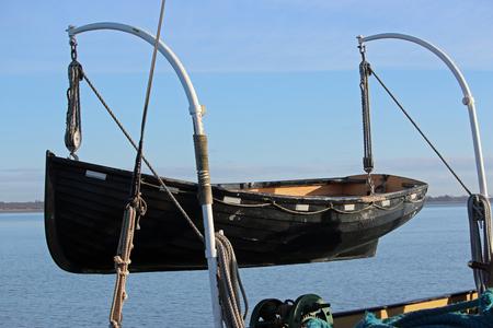 Schwarzes gemaltes hölzernes Rettungsboot auf Davits. Hintergrund von Fluss mit Bank im Abstand und im dunstigen blauen Himmel. Standard-Bild