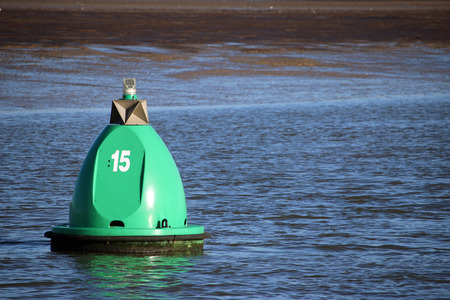 Green marker buoy floating on the River Stour in Suffolk, UK. Marked with the number 15. Background with river bank in the distance. Good copy space.