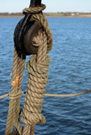 Rope and pulley on sailing ship with a background of river water and a river bank in the distance. Good copy space.