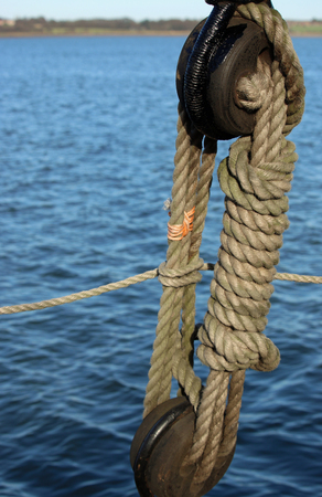 Rope and pulley on sailing ship with a background of river water and river bank in the distance. Good copy space.