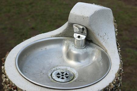 Fontaine de parc en métal avec bol sur un socle en béton avec un extérieur en galets pointillés. Banque d'images - 91502770