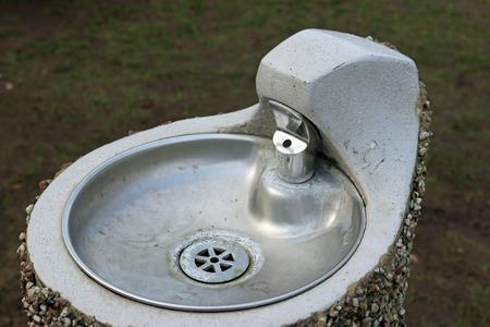 Fontaine de parc en métal avec bol sur un socle en béton avec un extérieur en galets pointillés. Banque d'images - 91720296