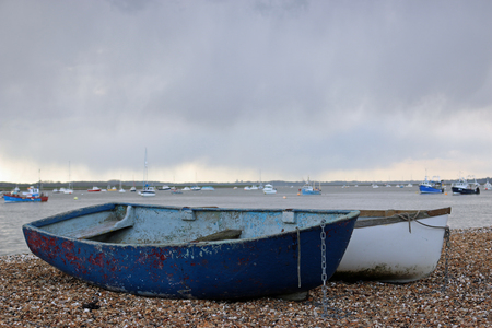 Two rowing boats used to get sailors to their boats hauled up on a river shingle beach with a grey rain cloud sky background and boats on the river.