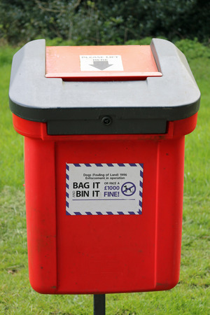 Red dog litter bin on a metal pole seen from the front with advisory sticker and black lid with red hinged chute. Background of parkland with grass lawn and trees. Stock Photo