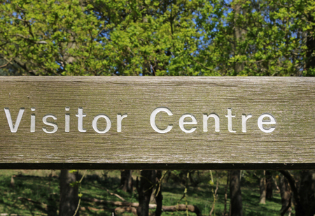 Routed wooden rustic visitor centre sign with the lettering inlaid in white on a wooden board with a background of blue sky and blurred trees in woodland. Stock Photo