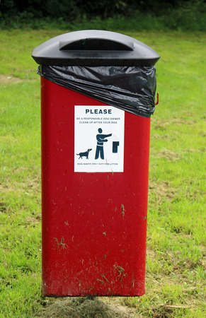 Red dog litter bin on a metal pole seen from the front with advisory sticker and hinged black lid in a park with grass. Banco de Imagens