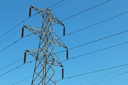 Hochspannungs-Strommast oder Kraftübertragungsturm mit Kabeln. Blauer Himmel im Hintergrund. Guter Kopierplatz. Standard-Bild