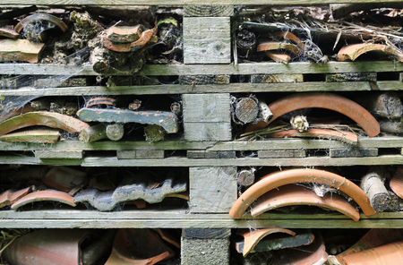 Bug hotel in a frame of wooden pallets containing logs, branches, tiles and broken clay flower pots .