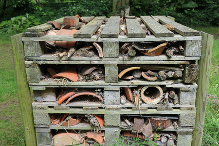 Bug hotel in a frame of wooden pallets containing logs, branches, bamboo stems and broken clay flower pots surrounded by grass with trees in the background.